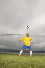 Male soccer goalie hitting ball with head