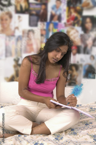 Teenage girl doing homework on bed