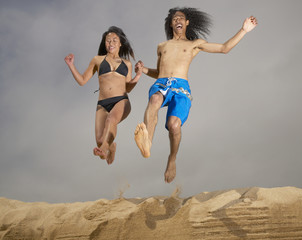 Couple jumping off sand
