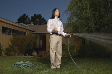 Man with garden hose watering yard