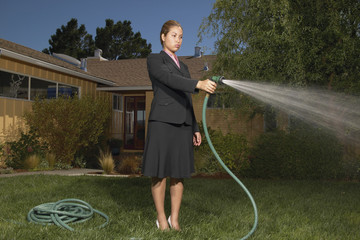 Businesswoman watering yard with garden hose