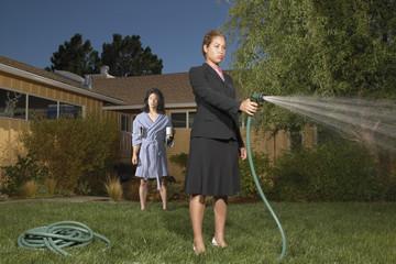 Businesswoman with garden hose in front yard