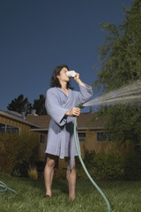 Man in robe watering grass