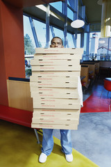 Teenage boy carrying stack of pizza boxes
