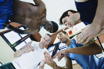 Low angle view of coach with basketball players in huddle