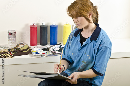Young female artist painting in studio
