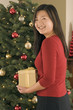 Teenage girl with gift by Christmas tree