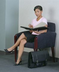 Businesswoman in chair with notebook