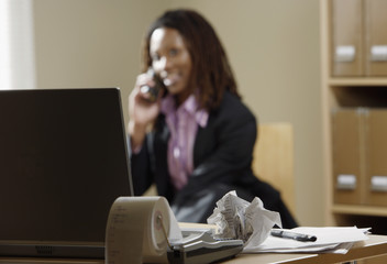 Businesswoman with laptop talking on phone