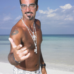Man with goggles and necklaces pointing at camera