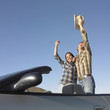 Couple in convertible celebrating