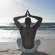 Man doing yoga at beach