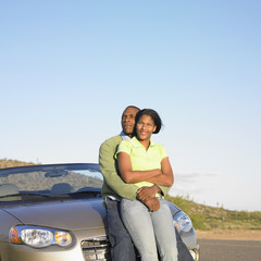 Couple hugging while sitting on hood of car