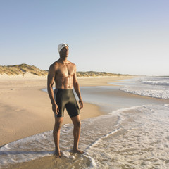 Man in swimming trunks and cap at beach