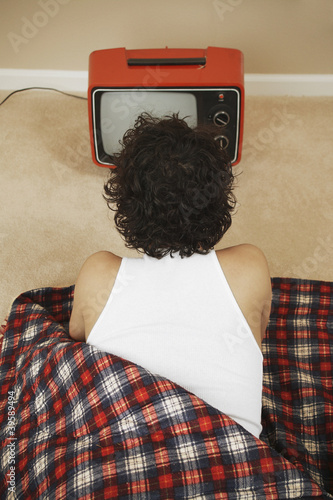 Young man in a sleeping bag watching TV