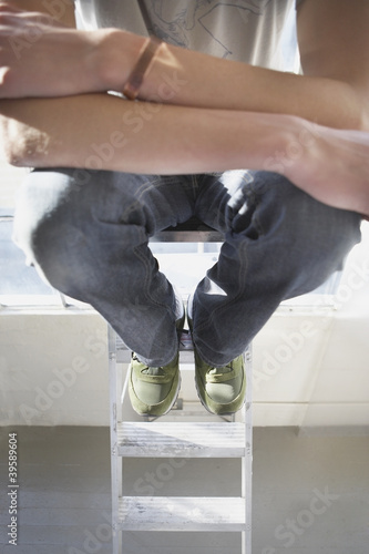 High angle view of man sitting on ladder