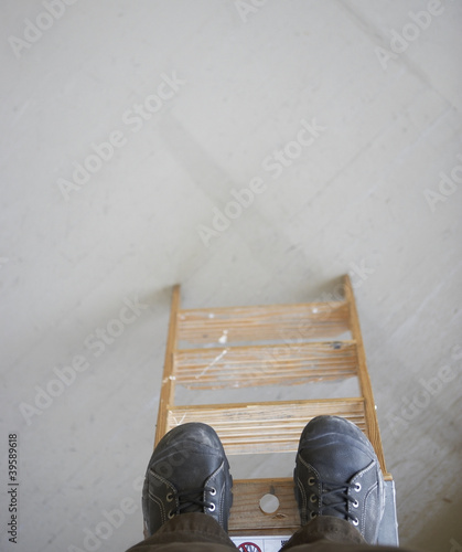 High angle view of man standing at top of ladder