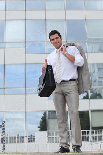 Businessman outside glass building holding satchel
