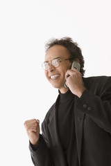Businessman celebrating while talking on cell phone