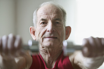 Portrait of elderly man lifting weights