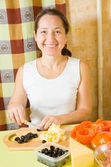 Woman cutting olive on cutting board