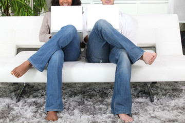 a couple in jeans using white laptops on a white sofa