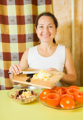 Woman adds grated eggs and  sliced olives in mince