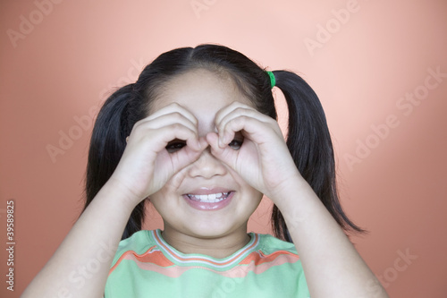 Young girl peeking out from inside curled fists