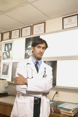 Male doctor standing with arms crossed