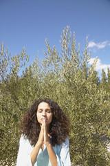 Young woman praying outdoors