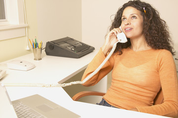 Businesswoman talking on phone at her desk