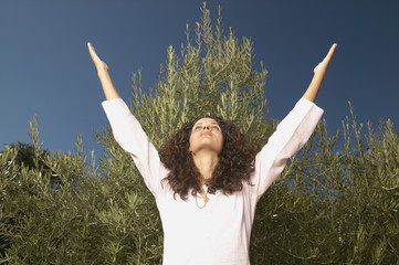 Young woman raising arms outdoors