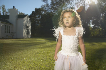 Young girl wearing a fairy costume in the backyard