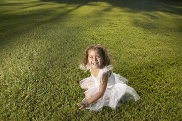 Young girl wearing a fairy costume outdoors