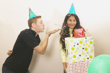 Young man blowing confetti on birthday girl