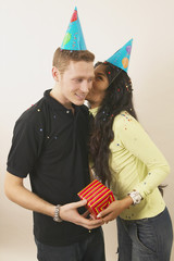Young woman kissing boyfriend while holding gift