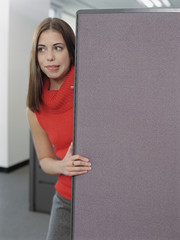 Businesswoman peeking out from behind cubicle wall
