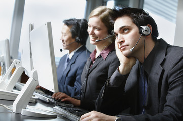 Three businesspeople talking on headsets