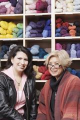 Portrait of two women in front of yarn