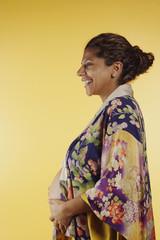 Pregnant woman wearing robe touching abdomen
