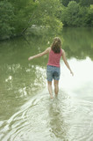 Rear view of woman walking in water