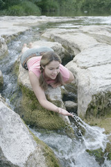 Young woman splashing water in a stream