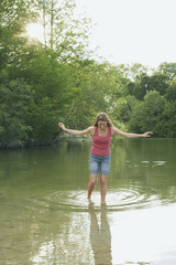 Young woman walks in the lake