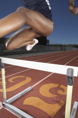 Female track athlete clearing a hurdle