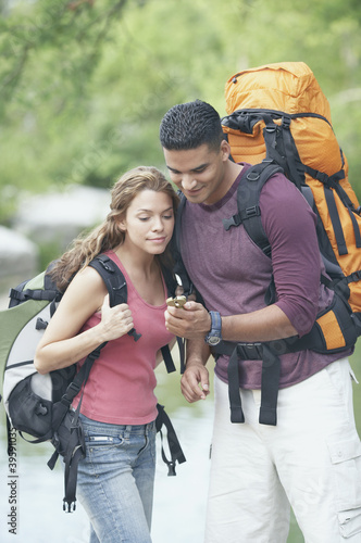 Hiking couple consulting a compass