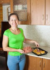 Woman stuffing vegetable marrow