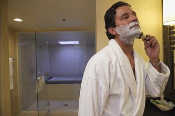 Man shaving before bathroom mirror