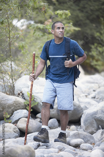 African American man hiking on rocks