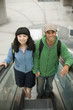 Young couple riding escalator