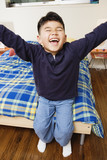 Boy sitting on bed and laughing